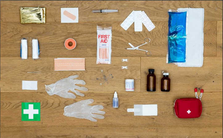 items in a first aid kit placed on wood